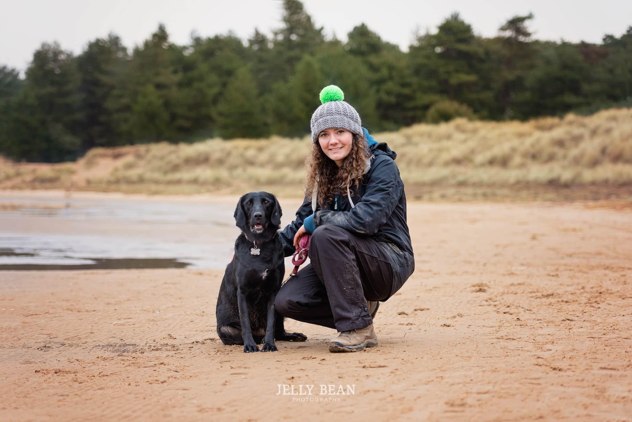 Girl with black dog on the beach