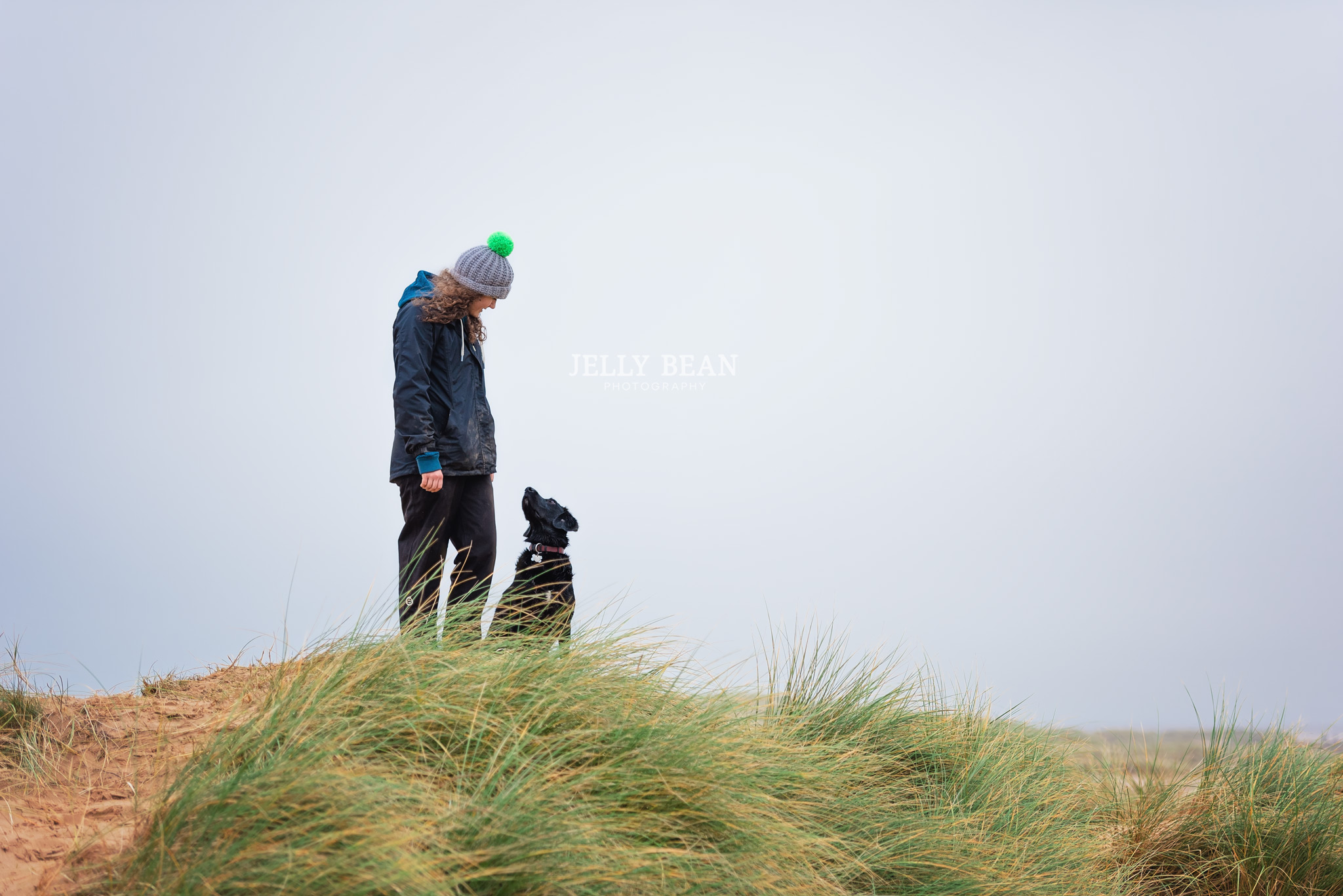 Dog and girl standing on top of sand dunes