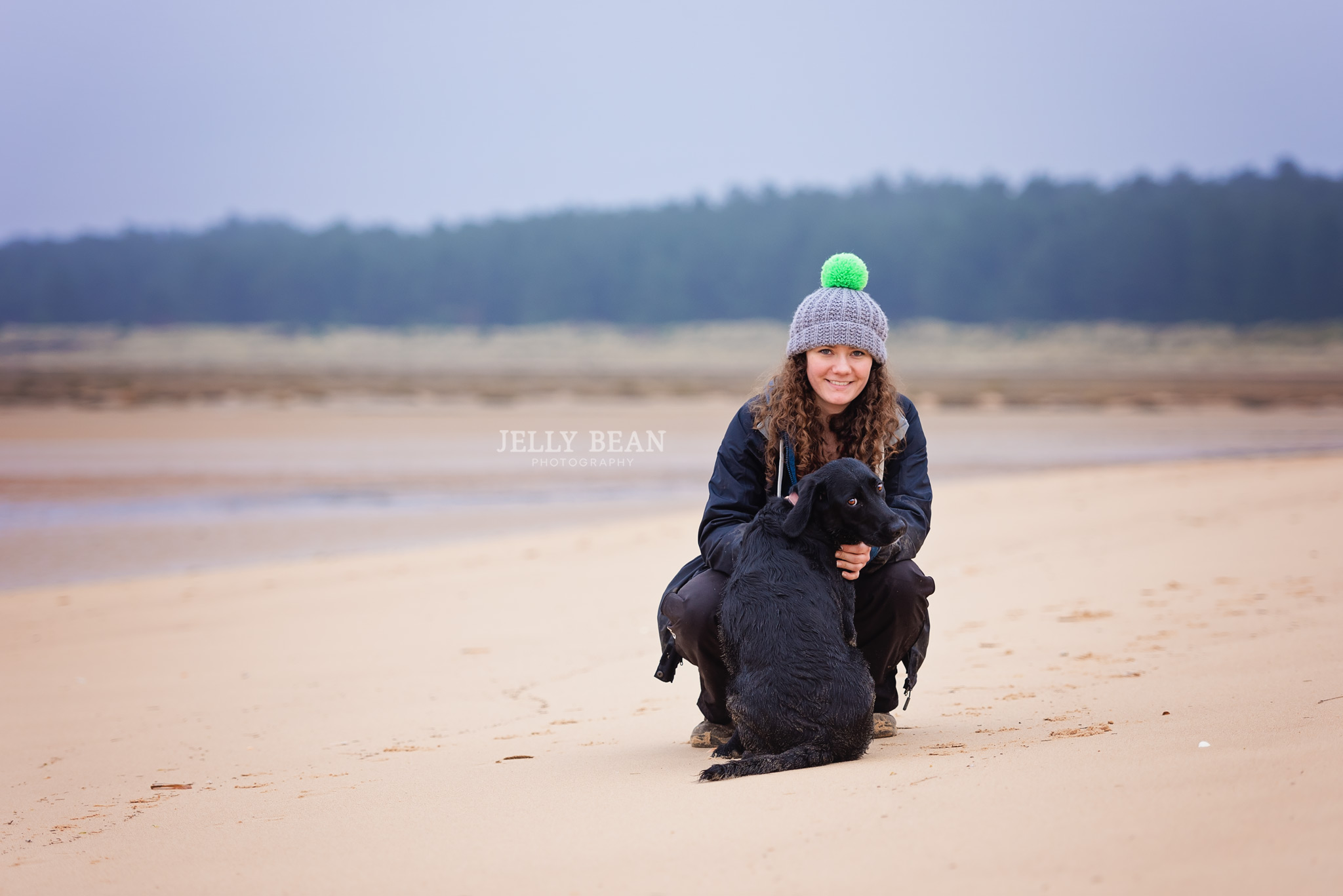 Girl and dog sitting on the beach