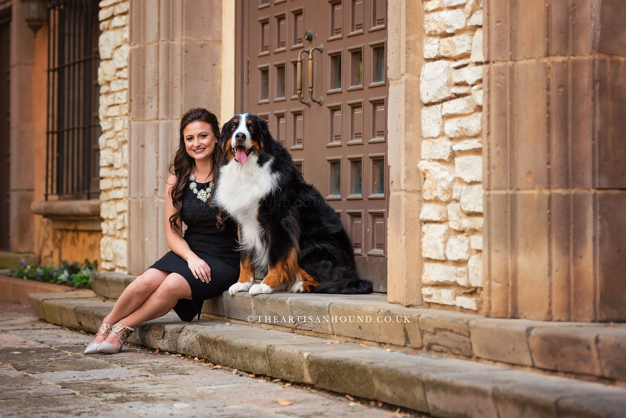 Dog and owner sitting in rustic doorway