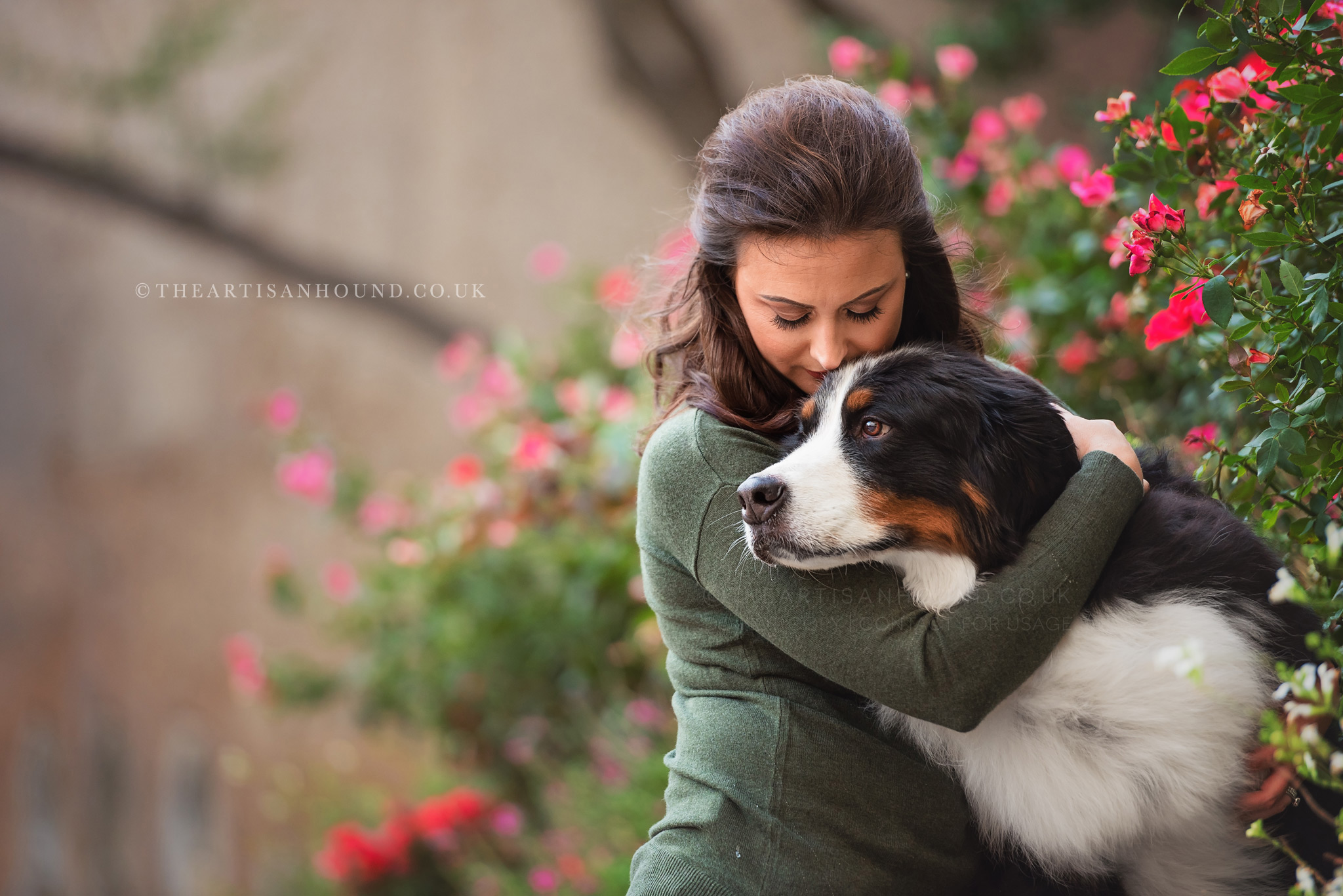 Owner hugging dog in flowers